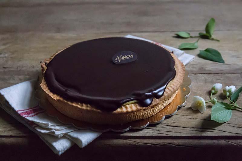Torta susanna di pasta frolla ripiena di ricotta e ricoperta di cioccolato fuso del Panificio Alinovi.